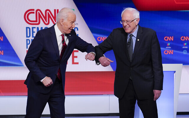 Former Vice President Joe Biden, left, and Sen. Bernie Sanders, I-Vt., right, greet one another before they participate in a Democratic presidential primary debate at CNN Studios in Washington, March 15, 2020. (AP/Evan Vucci)