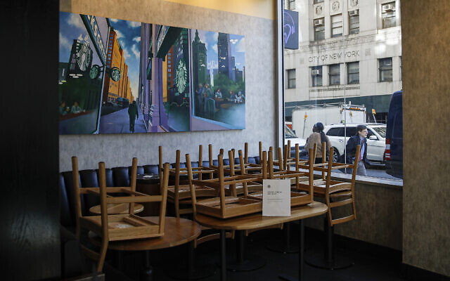 Chairs are stacked in a Starbucks coffee shop that remained open for customers purchasing for take-away, in New York, March 16, 2020. (John Minchillo/AP)