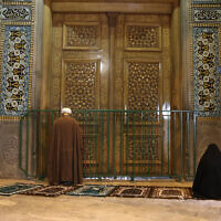 A cleric and a woman pray behind a closed door of Masoume shrine in the city of Qom, some 80 miles (125 kilometers) south of the capital Tehran, Iran, March 16, 2020. (AP Photo)