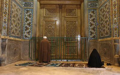 A cleric and a woman pray behind a closed door of the Fatima Masumeh shrine in the city of Qom, Iran, March 16, 2020. (AP Photo)