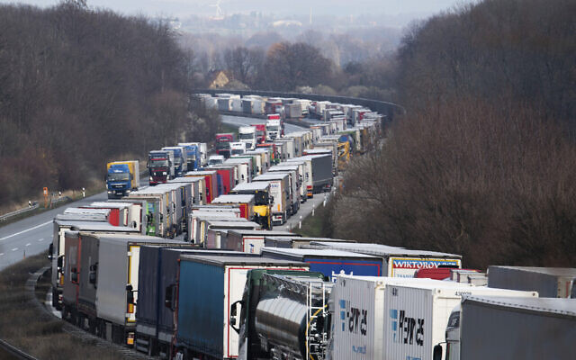 Trucks are jammed on the motorway A4  near Bautzen, Germany, Tuesday, March 17, 2020. Because of the controls at the border with Poland, a traffic jam formed on the Autobahn 4 between Dresden and Goerlitz, which, according to police, had grown to a length of 40 kilometers by noon.  (Robert Michael/dpa via AP)
