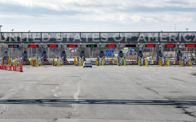 """A vehicle approaches the only open lane at the United States border crossing in Lacolle, Quebec, Wednesday, March 18, 2020. The Canada-U.S. border will be closed to non-essential traffic in both directions """"by mutual consent,"""" President Donald Trump confirmed Wednesday, as efforts across the continent to contain the widening COVID-19 pandemic continued to upend daily life in North America. (Ryan Remiorz/The Canadian Press via AP)"""