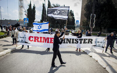 People wave Israeli flags, inverted Israeli flags and banners during a protest outside the Israeli parliament in Jerusalem, Thursday, March 19, 2020, accusing Prime Minister Benjamin Netanyahu's government of exploiting the coronavirus crisis to cement his power and undermine Israel's democratic foundations. (AP Photo/Eyal Warshavsky)