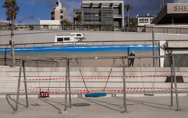 This March 19, 2020 photo shows swings at Tel Aviv's beachfront wrapped in tape to prevent public access. (AP Photo/Oded Balilty)