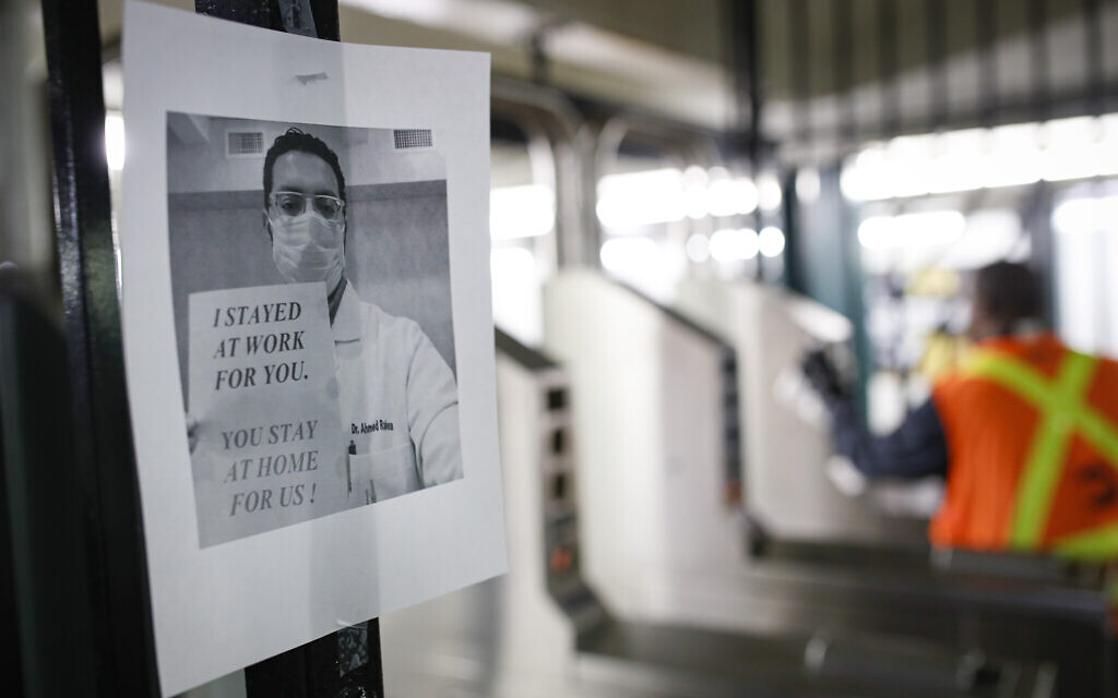 A flier urging customers to remain home hangs at a turnstile as an MTA employee sanitizes surfaces at a subway station with bleach solutions due to COVID-19 concerns, March 20, 2020, in New York. (AP Photo/John Minchillo)