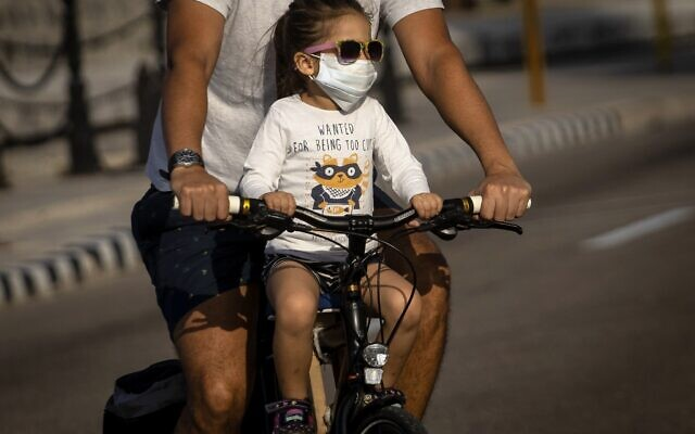 A girl wearing a protective face mask as a preventive measure against the spread of the new coronavirus ride a bicycle with her father in Havana, Cuba, Saturday, March 21, 2020. (AP Photo/Ramon Espinosa)