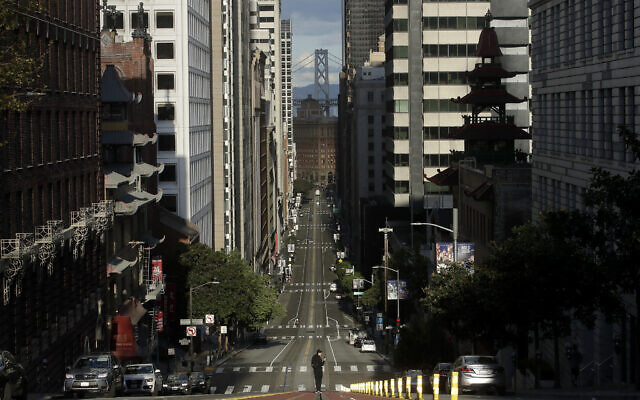 A man stands in the middle of cable car tracks on a near empty California Street in San Francisco, Saturday, March 21, 2020. (AP Photo/Jeff Chiu)