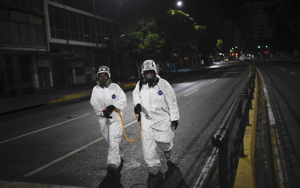 City workers walk after spraying disinfectant on the streets as a preventive measure against the spread of the new coronavirus, in Caracas, Venezuela, Saturday, March 21, 2020. (AP Photo/Matias Delacroix)