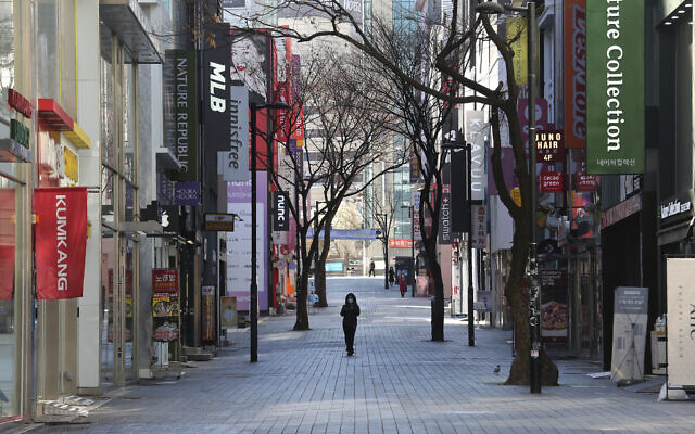 A woman wearing a face mask against the coronavirus walks along on a nearly empty shopping street in Seoul, South Korea, Sunday, March 22, 2020. (AP Photo/Ahn Young-joon)