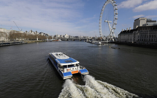 An empty tour boat on the River Thames in central London, with the London Eye wheel at right, Sunday, March 22, 2020. (AP Photo/Kirsty Wigglesworth)