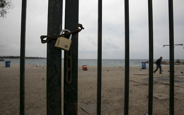 A padlock is seen on the entrance of a beach at the Alimos suburb of Athens, Sunday, March 22, 2020. Schools, restaurants, and other public places are already closed in the Greek capital aimed at slowing the spread of the new coronavirus, but other places like supermarkets, pharmacies and gas stations remain open. (AP Photo/Yorgos Karahalis)