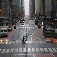 A commuter crosses 42nd Street in front of Grand Central Terminal during morning rush hour, March 23, 2020, in New York. (AP Photo/Mark Lennihan)
