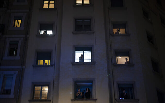 People applaud from their window in support of the medical staff working on the COVID-19 virus outbreak in Barcelona, Spain, Monday, March 23, 2020.  (AP Photo/Felipe Dana)