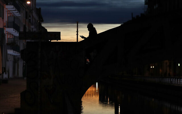 In this March 10, 2020 file photo, a woman wearing a face mask checks her phone as she walks at the Naviglio Grande canal in Milan, Italy. Across Europe, governments are increasingly using surveillance to try to curtail the lethal spread of the new coronavirus, tracking people's movements with aggregated cell phone location data and introducing apps to keep the infected quarantined. (AP Photo/Antonio Calanni)