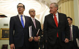 US Treasury Secretary Steven Mnuchin, left, accompanied by White House Legislative Affairs Director Eric Ueland and acting White House chief of staff Mark Meadows, speaks with reporters as he walks to the offices of Senate Majority Leader Mitch McConnell on Capitol Hill in Washington, March 24, 2020. (AP Photo/Patrick Semansky)