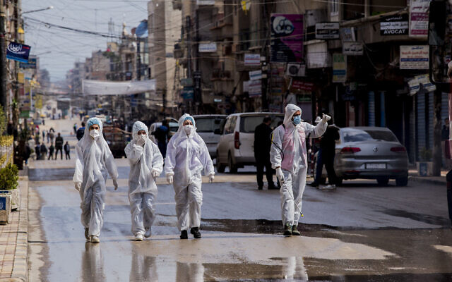 Medical workers oversee the disinfection of the streets to prevent the spread of coronavirus in Qamishli, Syria on March 24, 2020. (AP/Baderkhan Ahmad)