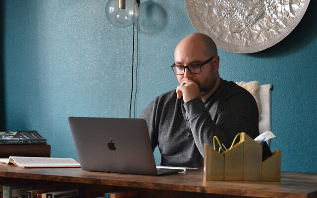 In this photo provided by Brett Seidl, Jonathon Seidl sits in his home office in Dallas on March 18, 2020 (Brett Seidl via AP)