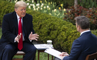US President Donald Trump talks with host Bill Hemmer during a Fox News virtual town hall with members of the coronavirus task force, in the Rose Garden at the White House, March 24, 2020, in Washington. (AP Photo/Evan Vucci)