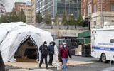 Medical Examiner personnel and construction workers are seen at the site of a makeshift morgue being built in New York, Wednesday, March 25, 2020.  (AP Photo/Mary Altaffer)