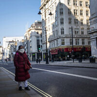 "A woman walks down the Strand during ""rush hour"" in Westminster, London, March 26, 2020. (Victoria Jones/PA via AP)"