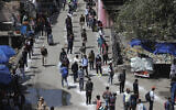 Passengers stand in a queue maintaining physical distance as they wait for transport being arranged by the government during lockdown in Jammu, India, March 26, 2020. (AP Photo/Channi Anand)