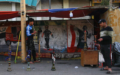 In this Thursday, March 19, 2020 photo, a man smokes waterpipe at Tahrir square, Baghdad, Iraq (AP Photo/Khalid Mohammed)