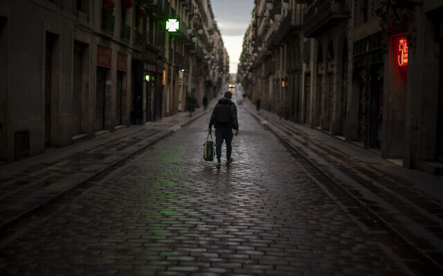 A man walks along an empty street in downtown Barcelona, Spain, March 26, 2020 as a lockdown to combat the spread of coronavirus continues. (AP Photo/Emilio Morenatti)