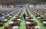People in protective clothing walk past rows of beds at a temporary 2,000-bed hospital for coronavirus patients set up by the Iranian army at the international exhibition center in northern Tehran, Iran, March 26, 2020. (AP Photo/Ebrahim Noroozi)