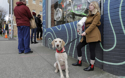 In this photo taken March 24, 2020, Mia Grace, right, holds a package of toilet paper as she and her dog Breezy observe social distancing chalk marks on the sidewalk while waiting to get in to The Reef Capitol Hill, a marijuana store in Seattle, which was limiting the number of people in the store at one time to help slow the spread of the new coronavirus. (AP/Ted S. Warren)