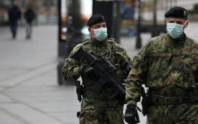 Serbian army soldiers patrol in Belgrade's main pedestrian street, in Serbia, March 26, 2020. (Darko Vojinovic/AP)