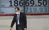 A man walks by an electronic stock board of a securities firm in Tokyo, March 30, 2020. (AP Photo/Koji Sasahara)