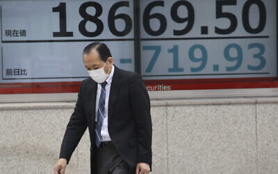 A man walks by an electronic stock board of a securities firm in Tokyo, March 30, 2020. (AP Photo/Koji Sasahara)