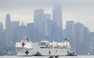 The Navy hospital ship USNS Comfort passes lower Manhattan on its way to docking in New York, Monday, March 30, 2020. The ship has 1,000 beds and 12 operating rooms that could be up and running within 24 hours of its arrival on Monday morning (AP Photo/Seth Wenig)
