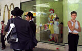 People stand outside a branch of  McDonald's in downtown Jerusalem in this file photo. The company has temporarily shut down its branches in Israel due to the coronavirus. (AP Photo/David Guttenfelder)