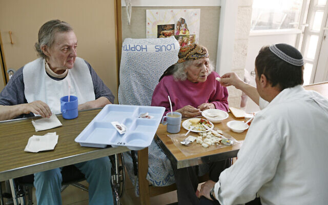 Illustrative: Asia, left, looks on as Eva, a Jewish patient takes bread after Rabbi Gabi, right, blesses it with a traditional Jewish blessing at the hospice at the St. Louis Hospital in Jerusalem, April 1, 2008. (AP Photo/Tara Todras-Whitehill)