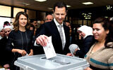 This photo from the official Facebook page of the Syrian Presidency shows Syrian President Bashar Assad casting his ballot in the parliamentary elections, as his wife Asma, left, stands next to him, in Damascus, Syria, April 13, 2016. (Syrian Presidency via AP, file)