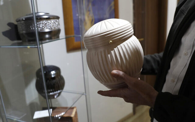 Illustrative: A man holds an urn at a cremation funeral parlor in Rome, October 25, 2016. (AP Photo/Alessandra Tarantino)