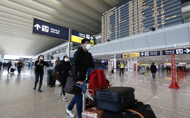 Illustrative: Passengers and airport staff wear masks at Rome's international airport, in Fiumicino, January 31, 2020. (Cecilia Fabiano/LaPresse via AP)