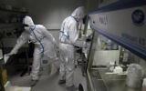 French lab scientists in hazmat gear inserting liquid in test tube manipulate potentially infected patient samples at Pasteur Institute in Paris, February 6, 2020. (Francois Mori/AP)
