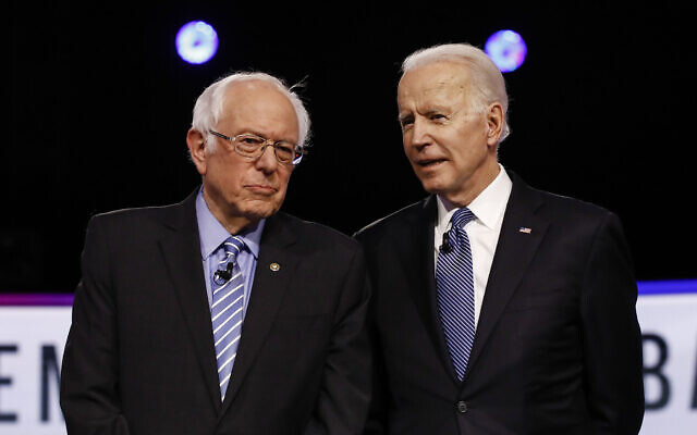 From left, Democratic US presidential candidates Bernie Sanders and Joe Biden, talk before a Democratic presidential primary debate, February 25, 2020, in Charleston, South Carolina. (AP Photo/Matt Rourke)