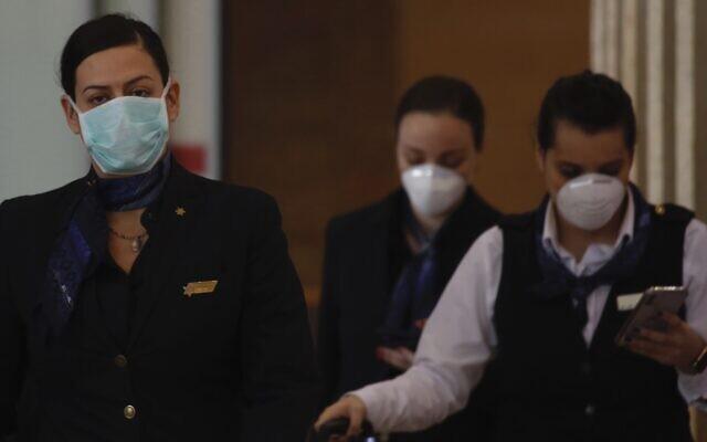 El Al employees wearing protective masks arrive  in Ben Gurion airport near Tel Aviv, Israel, Thursday, Feb. 27, 2020. (AP/Ariel Schalit)