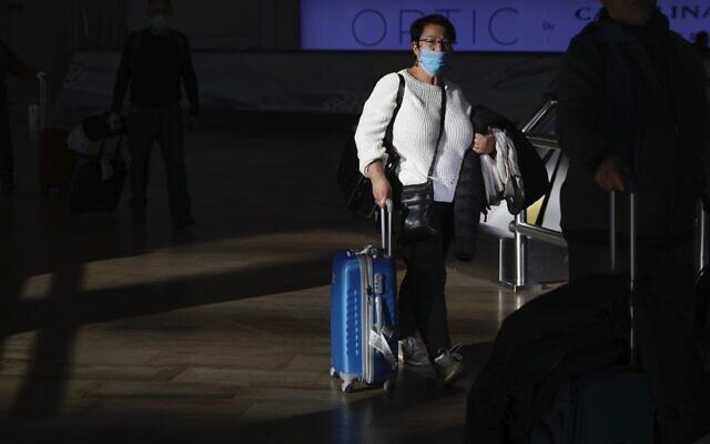 A woman wearing a protective mask arrives in Ben Gurion Airport, near Tel Aviv, Israel, Thursday, Feb. 27, 2020. (AP/Ariel Schalit)