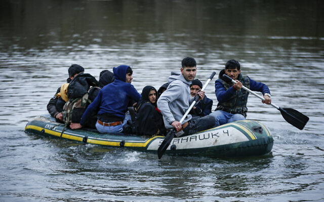 Migrants use an inflatable boat as they attempt to enter Greece from Turkey by crossing the Maritsa river near the Pazarkule border gate in Edirne, Turkey, February 29, 2020. (Emrah Gurel/AP)