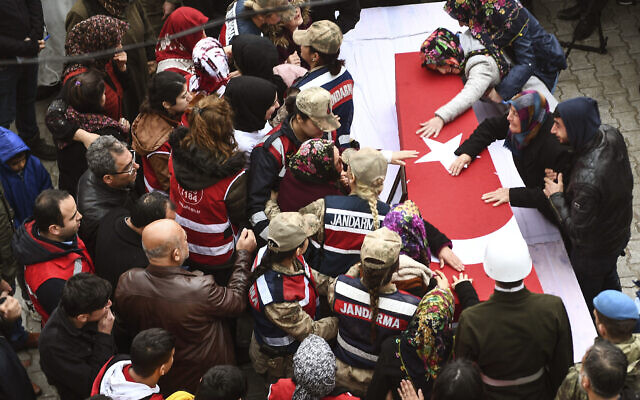 People react by the coffin during a funeral ceremony for Emin Yildirim, one of the 36 Turkish soldiers killed on Thursday in a Syrian army attack in the Idlib area of Syria, in Hatay, Turkey, Saturday, Feb. 29, 2020. (AP Photo)