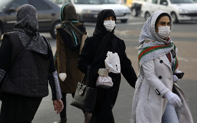 """Pedestrians wearing face masks cross a square in western Tehran, Iran, February 29, 2020. Iran is preparing for the possibility of """"tens of thousands"""" of people getting tested for the new coronavirus as the number of confirmed cases spiked again Saturday, Health Ministry spokesman Kianoush Jahanpour said, underscoring the fear both at home and abroad over the outbreak in the Islamic Republic. (AP Photo/Vahid Salemi)"""