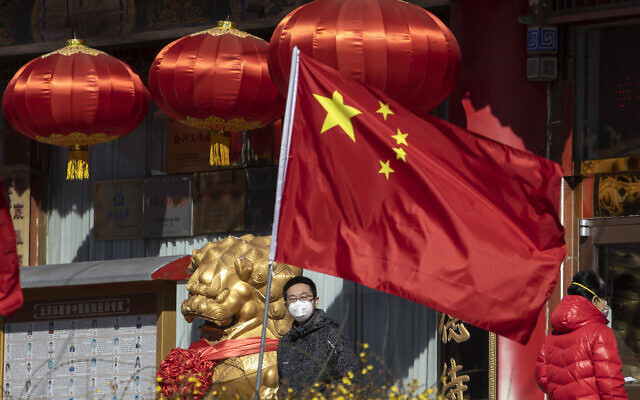 A masked man looks out near a national flag outside a traditional medicine hospital in Beijing on Tuesday, March 3, 2020 (AP Photo/Ng Han Guan)
