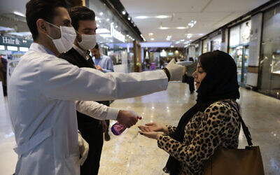 A woman has her temperature checked and her hands disinfected as she enters the Palladium Shopping Center in northern Tehran, Iran, March 3, 2020. (Vahid Salemi/AP)