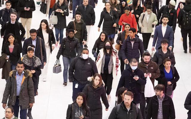 Three commuters, center, wear masks as they walk through the World Trade Center transportation hub, March 4, 2020, in New York. (AP Photo/Mark Lennihan)