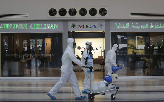 Workers wearing protective gear walk in front of the Middle East Airlines office as spray disinfectant as a precaution against the coronavirus outbreak, in the departure terminal at the Rafik Hariri International Airport, in Beirut, Lebanon, Thursday, March 5, 2020. (AP/Hassan Ammar)