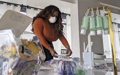 Adilisha Patrom, owner of a co-working and event space next to Gallaudet University, organizes face masks, hand sanitizer and other supplies inside her pop up shop on March 5, 2020, in Washington (AP Photo/Nathan Ellgren)